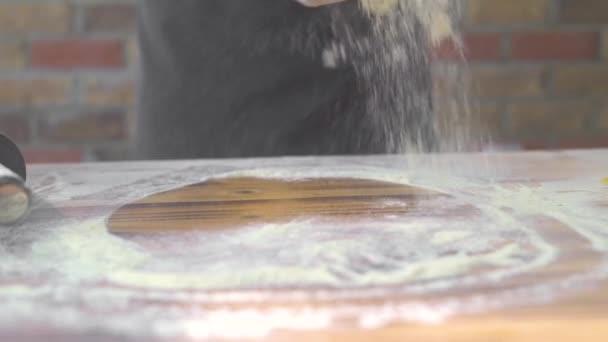 Az ember permetezés lisztet asztalra gördülő pizza tésztát. Chef szakács hogy tésztát rakott sütemény konyhában sütőházban. Főzés sütemény, torta és pite. Egészséges, házias ételek.