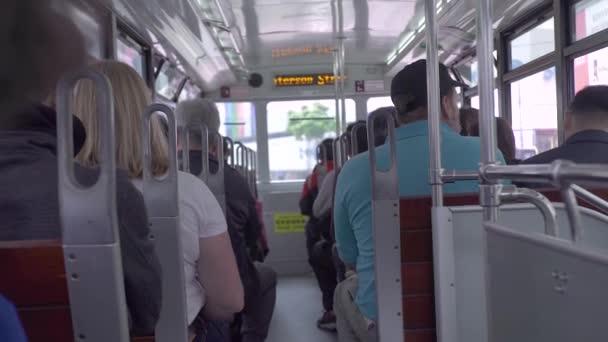 Cestující na sedadle jízdy tramvají na ulici moderního města. Zpětné zobrazení osob sedícího na sedadlech pro jízdu v městské tramvaji v moderním městě.