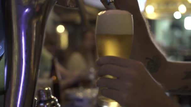 Barmana nalijí pivo na sklo z pivního kohoutku v baru. Zavřete brewerské ručičky a nalijete ji na sklo ze rukojeti.