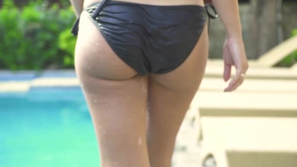 Wet sexy buttocks on black bikini. Attractive woman in wet panties walking on swimming poolside in resort hotel. Female ass back view. Sensual female body in swimming bikini.