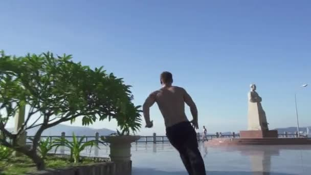 Acrobat practicing parkour jump on urban street. Free runner man training trick and stunt in summer city. Active youth lifestyle. Parkour and freerunning. Extreme sport outdoor