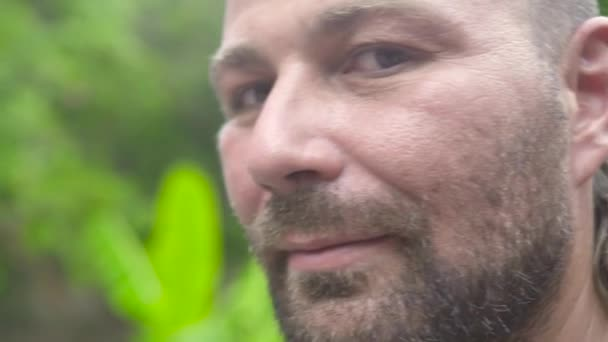 Close up face handsome bearded man looking to camera and smiling. Portrait adult man with bristly face.