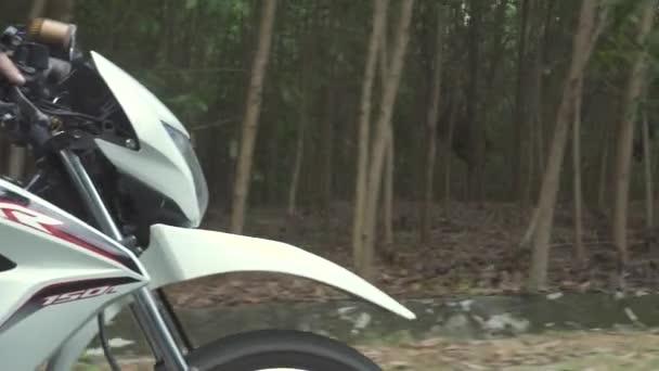 Motocyklista jezdí na motocykl po silnici, zatímco Moto cestuje. Motorkářův muž, který jede na motorce na venkovské silnici. Motorka cestuje. Moto životní styl