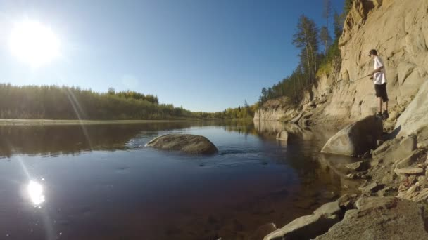 Időközű videó a mozgás a víz a folyó és a modern horgász egy forgó rúd az agyag a szikla a vad Taiga a Yakutia.