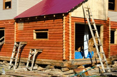 Construction of the facade of a new house made of pine timber with stairs leaning against the walls and Windows in Yakutia.