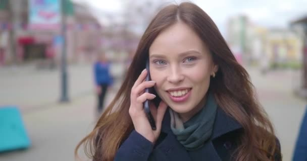 Attractive and cheerful young woman using a cell phone outside. She is talking on the phone and laughing. Crowded city street. Close up.