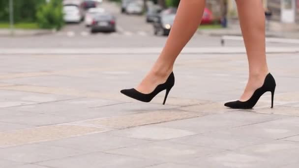 Female legs in high heels shoes walking in the urban street. Feet of young business woman in high-heeled footwear going in the city. Girl stepping to work. Slow motion Close up