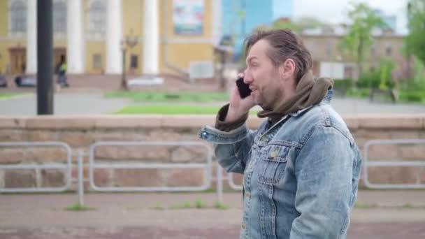 Muž v neformálním oblečení chodí po ulici a její BF na telefonu