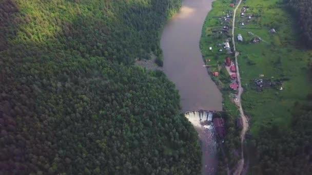 Luftaufnahme des Staudamms am Fluss mit Bäumen, die gelbes Laub bedecken.
