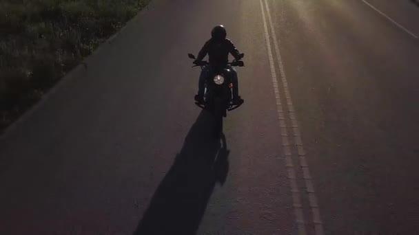Muž na motorce jezdí na silnici. Kamera se pohybuje zpět doprovázet jezdce. Video z dron.