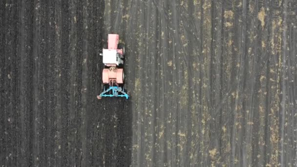 View from drone. Tractor plows a field. Agriculural concept.