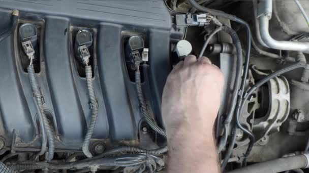 Closeup video of a male hand pouring an oil into a car engine.