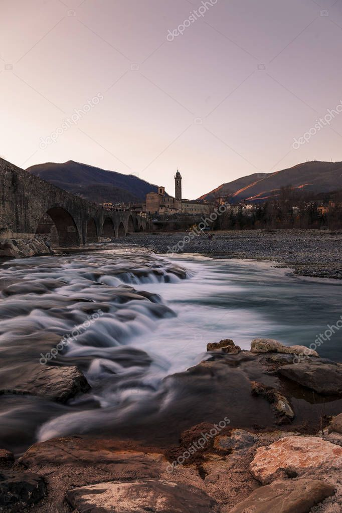 landscape of a medieval bridge over a turbulent river at sunset in winter
