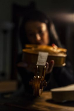young woman apprentice violinmaker checking the beauty of her violin