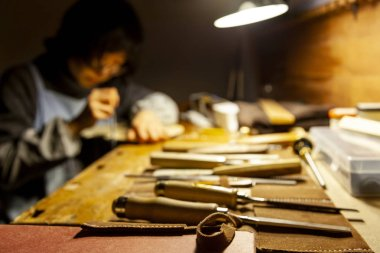 female artisan violinmaker while viewing a new violin in the laboratory