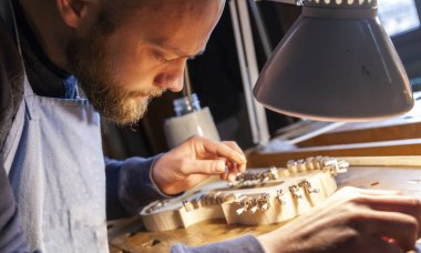 male craftsman violin maker working on a new violin in the workshop