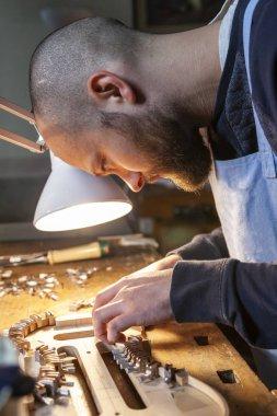 male craftsman violin maker working on a new violin in the workshop