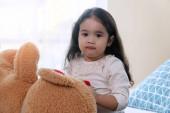 Vidám aranyos kislány nagy barna plüssmackóval az ágyon ülve, miközben a kamerát nézi a hálószobában. Életmód gyermek relaxációs koncepció