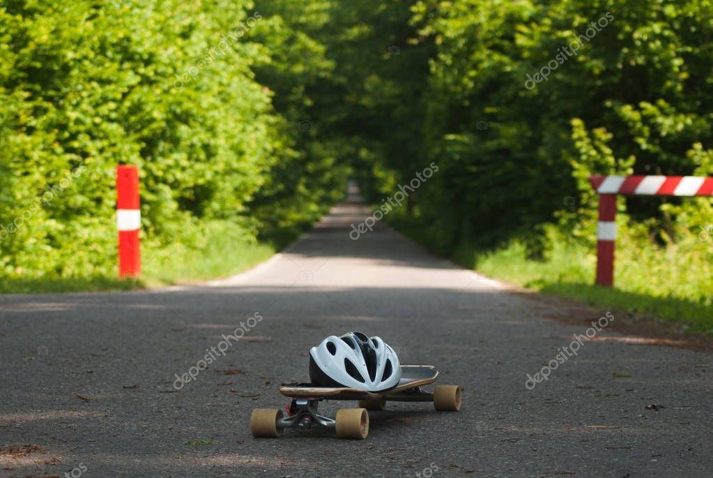 Forest road, skateboard and helmet,