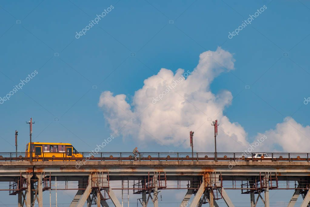 Yellow bus rides on the bridge, school bus on the sky background,