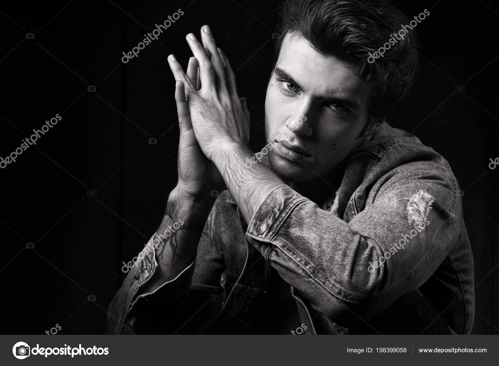 Closeup of black and white masculine portrait on a black background young handsome man posing and looking at camera fashion photograph professional model