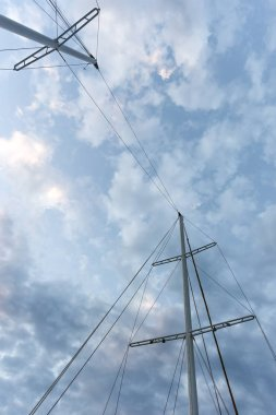 The mast of the ship on a twilight sky. Background the end of the voyage