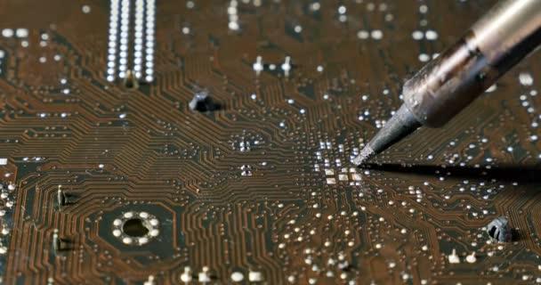 Forrasztó egy áramköri kártyán egy forrasztópáka. Közeli lövés a számítógépek és elektronikai szerviz javítás