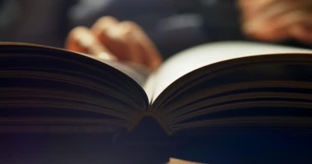 Nachts ein Buch lesen. Blätterende Buchseiten. Nahaufnahme