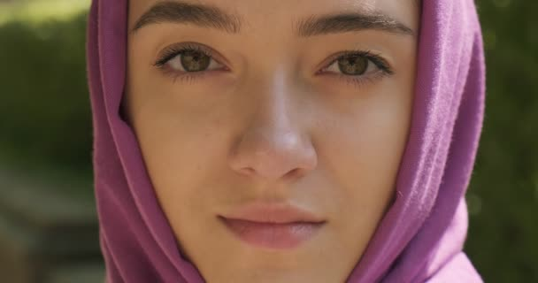 Beautiful young woman looking at camera, wearing traditional headscarf. Attractive Female in hijab. Close up