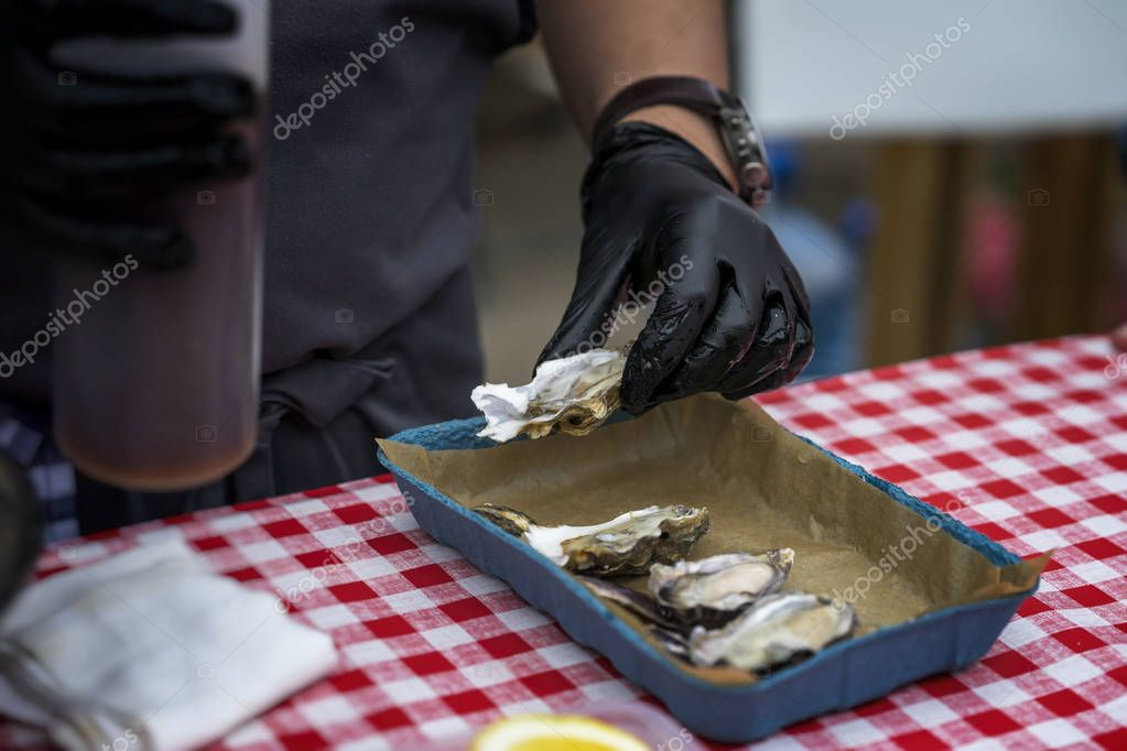 Preparation and sale of fresh oysters, mans hands in black gloves, seafood market. Gastronomic gourmet dainty products on market counter, real scene, food market