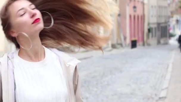 Mladá dívka s dlouhými vlasy, červené rty a velký kruh náušnice na ulici ve Varšavě