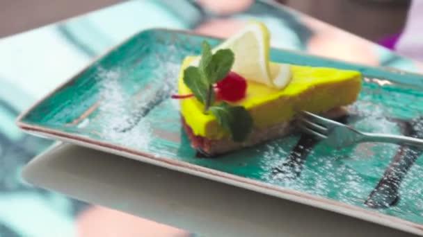 Pohár z růžové latte káva s žlutá citron dezert s cherry, máta a vidličkou na zelené štítku v kavárně