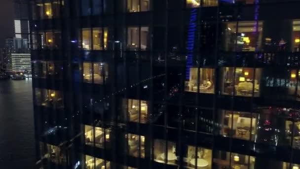 Deriva aerea prima notte windows hotel appartamenti camere moderni grattacieli cittá Shanghai China Glass riflesso illuminazione variopinta Huangpu River embankment crociera nave futuristica urbana. Drone