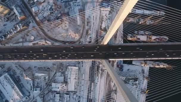 Letecká shora dolů malebná zlatá Zavěšený most mezi stožáry silniční aktivní provoz auta Horn Bay lodí městské moderní architektury Vladivostok Asie. Cestovní mezník sněhové západ slunce v zimě. DRONY 4k