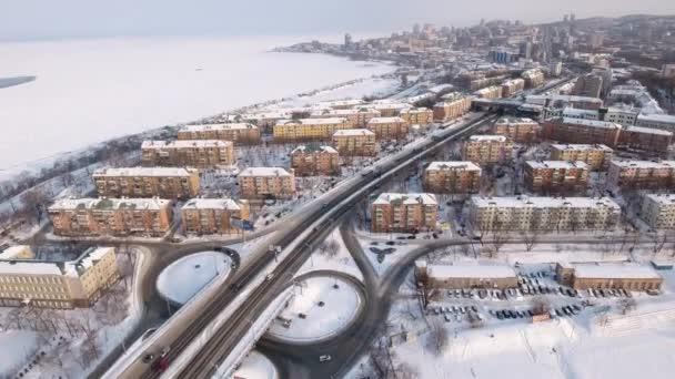 Téli hó napsütéses napon. Drone légi gyorsított aktív közúti forgalom autók cseréje logisztika. tipikus szovjet városkép Vlagyivosztok utcai házak Hills parti quay tenger fagyott a jég. Oroszország.