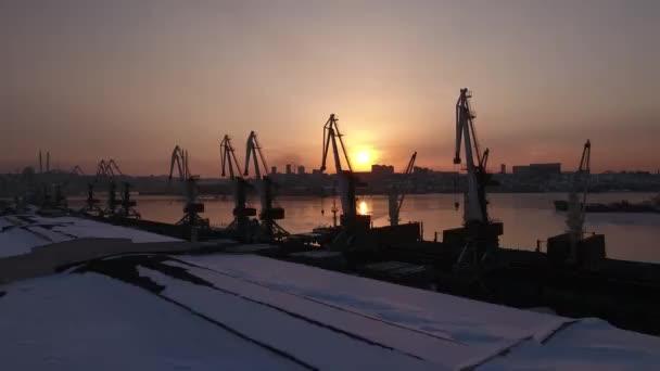DRONY vpřed mezi jeřáby silueta oranžové slunce nad přístavní město komerční nákladní zařízení. Ocelové konstrukce průmyslové. Zlatý roh ledově chladný. Vladivostok Primorskiy Rusko. Zimní sníh. DRONY 4k