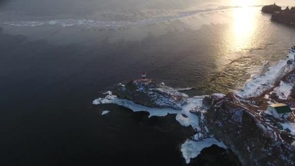 Aerial Top Basargin Peninsula Scenic lighthouse tower Main Sea gate Navigation Symbol Rocky isthmus. Sea coastal nature amazing. Vladivostok Russia Travel landmark Winter snow sunset reflection. Drone
