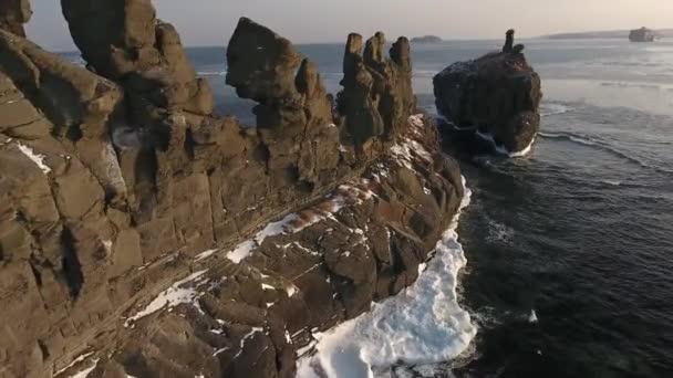 Letecká dopředném letu malebnými útesy Basargina hřebenu přírodní vlny pobřežní zmrzlé moře oceánu obzoru romantické krajině modré. Vladivostok Asie. Cestovní turistická atrakce. Zimní slunce sníh. Vrtulník