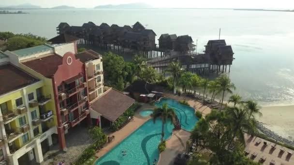 Letecká dopředného letu populární hotely Langkawi. Elita drahé. Rekreační oblast bazén palm stromy exotické pláže bílého písku. Lidé turistů plavání. Jedinečné dřevěné domy stojí ve vodě moře vody Horizont