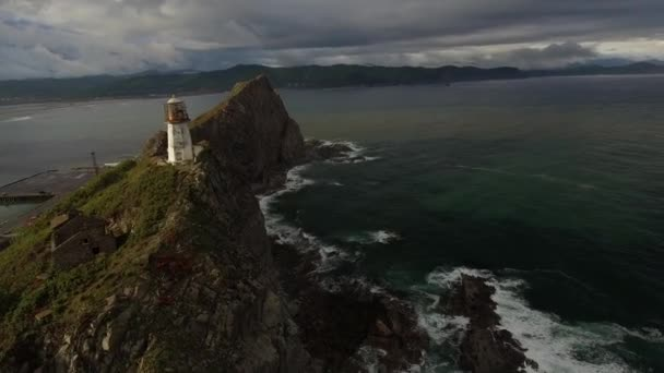 Wild wind storm white old lighthouse on colorful beautiful cape Brinera. Helicopter drone cinematic flight approach. Freedom no one. Epic cinematic sunset light. Great ocean waves sea. Russia north