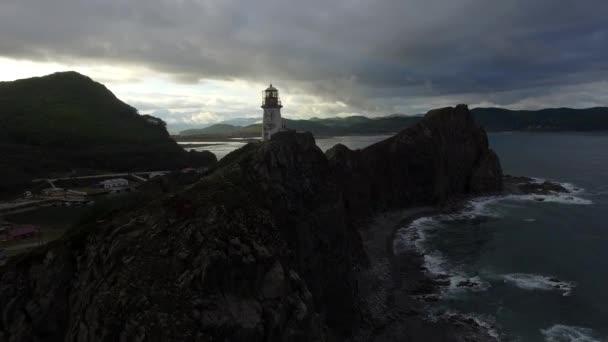 Dopředném letu letecká dron uzavřít starý maják na temné vysoké skály. Tlumené světlo bouřlivých mračen. Vyhlídkové večerní horor. Rusko Dálného východu pobřeží mysu Brinera. Japonské moře oceánu vlny silný vítr.