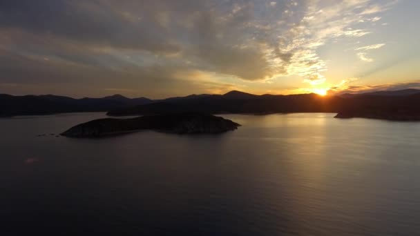 Aerial Scenic orange sunset sun bright rays Natural landscape. Islands silhouette. Sea ocean calm reflection in water. Sky multi-colored clouds. Open space horizon Mountains hills. Romance journey.