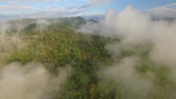 Krásnou podzimní krajinou přes mraky bílé Oblačno mlhy. Les pokrývá pohoří. Vrcholky kopců. Příroda divočiny z velké výšky. Romantický klid. Modrá obloha horizont. Cestovní ruch. Letecká vpřed