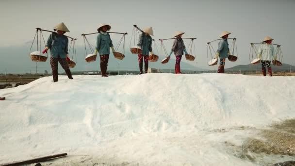 V nádobách se z nich nalévá sůl cinematických dělníků v horské skupině s bílým solí. Profese autentický kuželový klobouk. Historické tradice produkce chudého Vietnamu. Gimbalový přístup