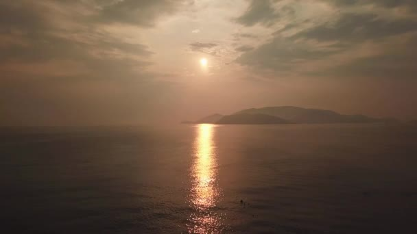 Beautiful epic orange sunset sky from high altitude over calm sea ocean. Clouds heaven. Mountain background. Natural seascape horizon. Sun reflected water brilliant path. Wild untouched. Aerial Drone