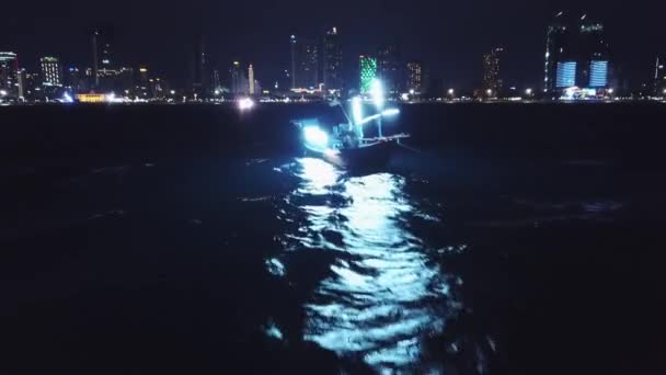 Night lights fishing old ship boat. Strong waves reflection swinging people fishermen pulling rod attract squid. Sea ocean cityscape modern city background. Vietnam Asia Nha Trang. Aerial low forward