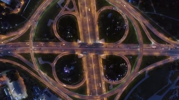 Helicopter epic round road junction with a night beautiful pattern of illuminated modern Moscow urban roads. Traffic intersection in metropolis. Many cars travel fast directions. Lift up altitude 4K