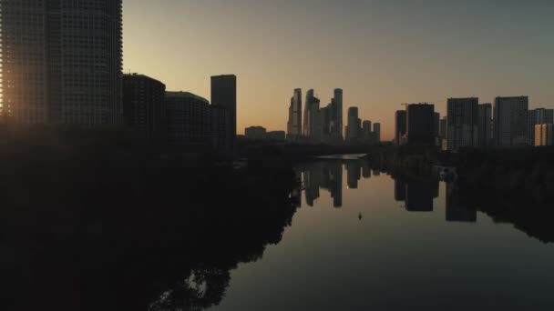 Légi előre Moszkva város felhőkarcolók napkeltekor sziluett tükröződés a folyóban. Modern üzleti negyed. Gazdag, drága ingatlanfejlesztés. Felhőtlen narancssárga égbolt horizont. Oroszország