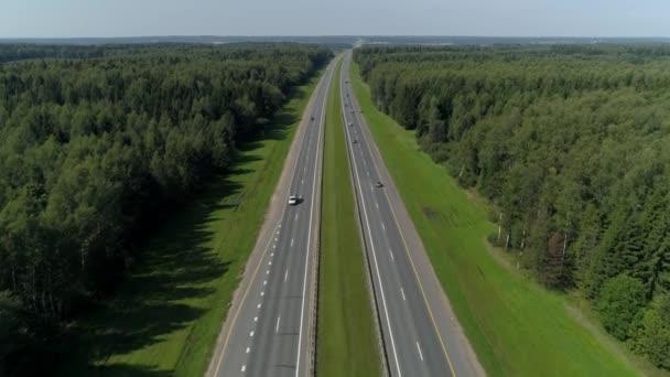 Drone rovné asfaltové silnice. Spousta aut jezdí vysokou rychlostí. Dálnice opouští horizont kvůli venkovské přírodní krajině mezi lesy. Chase Travel Logistics svoboda. Letecký posun