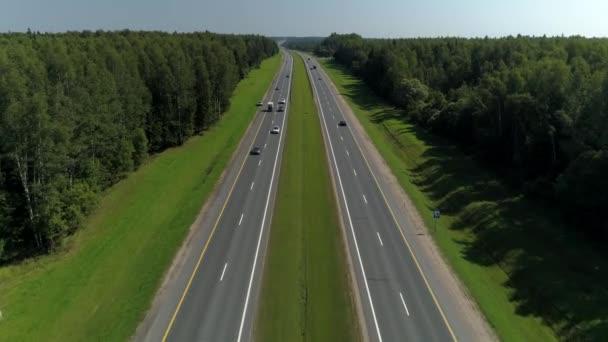 Vzduch z velké výšky země dálnice mezistátní dálnice asfalt dvě silnice z města obousměrné jít do dálky mezi zeleným lesem. Aktivní silniční provoz. Krajinný horizont. Slunečný den